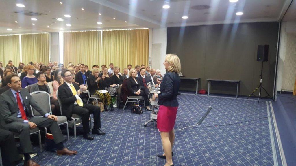 Sue speaking on stage in Munich
